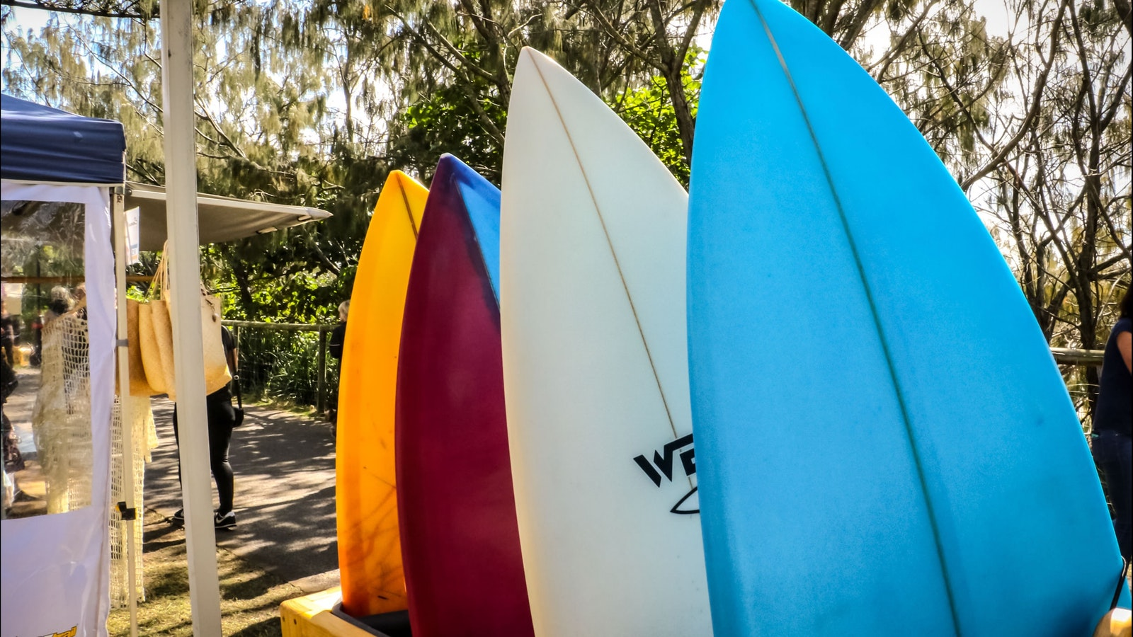 four brightly coloured surf boards on a hand made rack